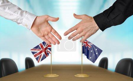 Photo pour Deux diplomates du Royaume-Uni et en Australie qui s'étend de leurs mains pour une poignée de main sur un accord entre les pays. - image libre de droit