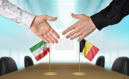 Photo pour Deux diplomates de l'Iran et de la Belgique qui s'étend de leurs mains pour une poignée de main sur un accord entre les pays. - image libre de droit