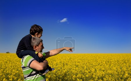 Father and son looking on rapeseed field on summer day.Father and son  looking  over a bloom canola fields
