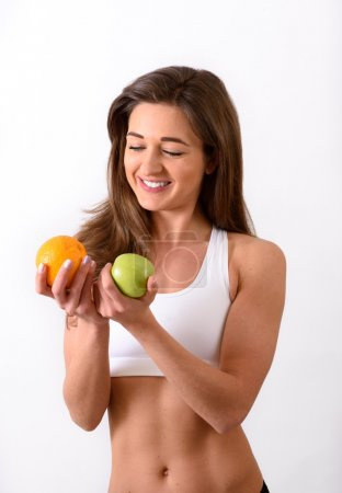 Young slim woman in sports top holding orange and apple