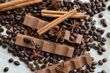 Photo for Bar of dark chocolate, milk chocolate bar, coffee beans, star anise, cinnamon sticks, seasonings, spices, close-up on a white wooden background - Royalty Free Image