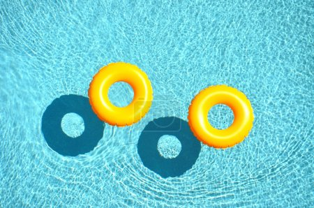 Photo for Yellow pool float, pool ring in cool blue refreshing blue pool, room for your text - Royalty Free Image