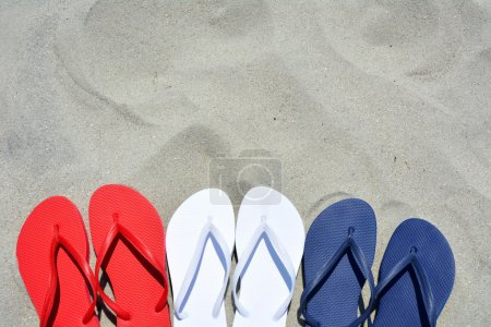 Red white and Blue flip flops on the sand Plenty of room for your text