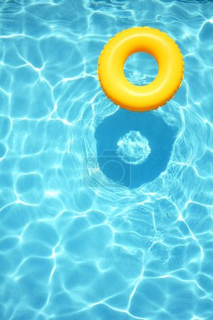 Photo for Yellow pool floats, rings in a cool blue refreshing swimming pool. Room for your text. - Royalty Free Image