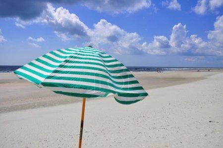 Pretty beach scene with striped umbrella....