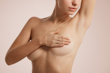 Closeup cropped portrait young woman with breast pain touching chest colored isolated on background