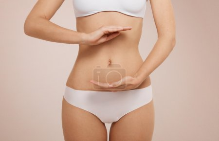 Woman showing sign bio balance on her stomach isolated