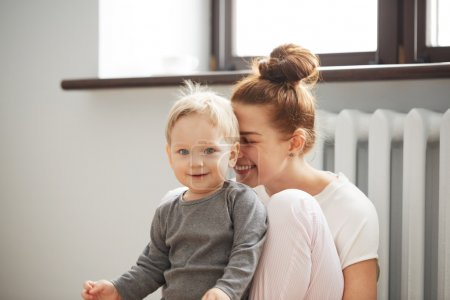 Happy young mother with little son on bedroom home background