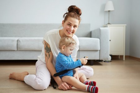 Young mother with her one years old little son dressed in pajamas are posing. Mom with son taking selfie on her smartphone or action camera in the bedroom.  Selective focus. Casual lifestyle photo.