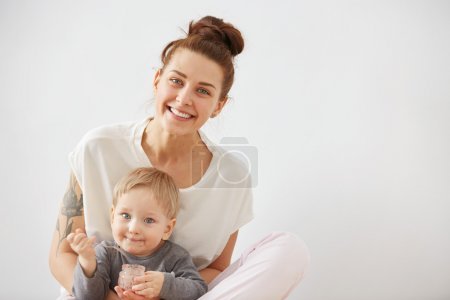 Young attractive mother with her one years old little son dressed in pajamas.  Boy eating a fruit smoothie himself in the bedroom at the weekend together, warm and cozy scene. Selective focus.