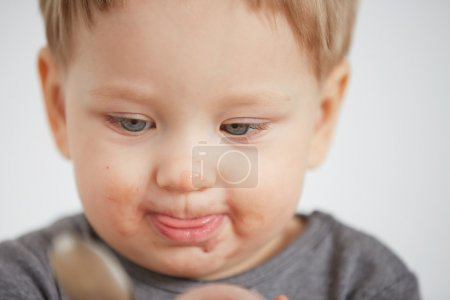 Cute little boy eating yogurt. Boy eating a fruit smoothie himself in the bedroom at the weekend , lazy morning, warm and cozy scene.