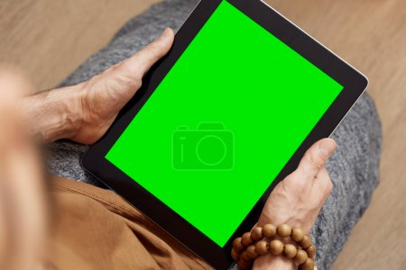 Man using digital tablet pc with green screen for internet and email. Adult man enjoys his digital tablet.