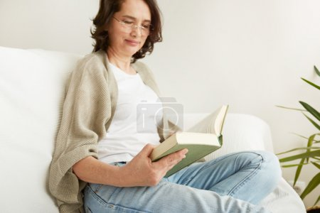 Charming mid age lady enjoying being at home and reading.