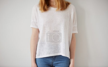 Young girl wearing blank t-shirt and blue jeans. Wall background