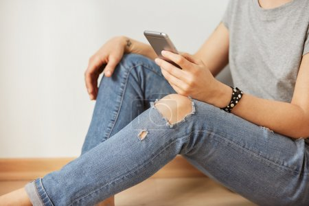 Closeup image of a teenager is searching information in network on mobile phone during free time. Young female student is revising photos on her cell telephone during break between lectures