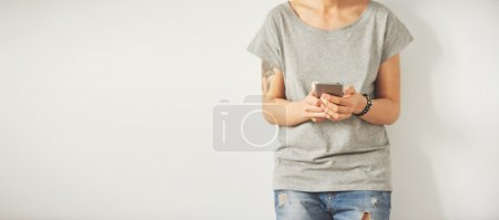 Beautiful hipster woman checking email via mobile phone while background with copy space for text message or promotional content, charming female holding cell telephone in hands while waiting friends.