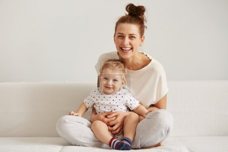 Mother and baby laugh together at home. They are sitting on the sofe in a brightly lit living room at the weekend together, lazy morning, warm and cozy scene. Selective focus
