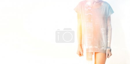 Closeup photo of stylish girl wearing blank t-shirt and looking down. Double exposure, panoramic view contemporary megalopolis background. Space for your business message. Wide, sunset effect