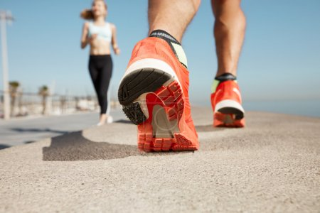 Sports background. Athlete runner feet running on road closeup on shoe. Man fitness jog workout wellness concept. Man runner legs and shoes in action on road outdoors at road near sea.