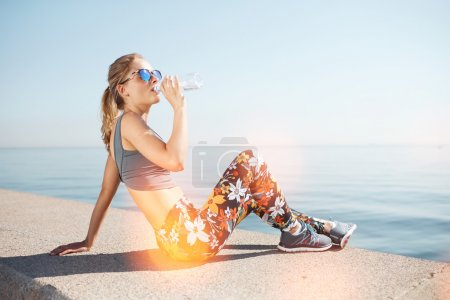 Muscular young female fitness blonde woman drinking water from bottle after running at beach. Woman sport runner resting taking a break with water bottle drink outside after training.