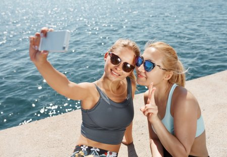Happy fitness selfie blonde girls smiling and taking self portrait photograph with smart phone after running exercise workout on beach.  Healthy lifestyle with fit Asian and Caucasian women.