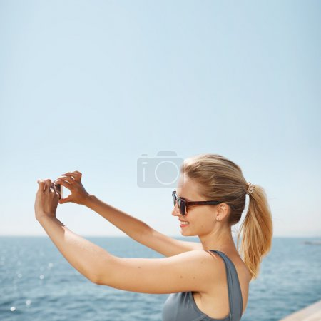 Happy fitness selfie blonde girl smiling and taking self portrait photograph with smart phone after running exercise workout on beach.  Healthy lifestyle concept with fit caucasian woman.