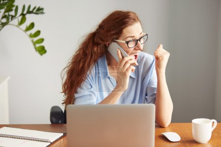 Headshot of a successful businesswoman looking excited talking on the cell phone. Portrait of a female freelancer shouting with excitement and joy. Attractive female manager winning business sitting i