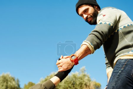 Helping hand - hiking girl get help from a smiling man focus at