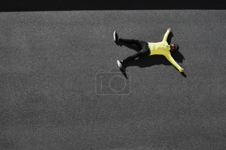 Top view runner in yellow sportswear resting lying on a black as