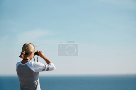 Woman tourist looking through binoculars at distant sea, enjoying landscape, copy space for your text