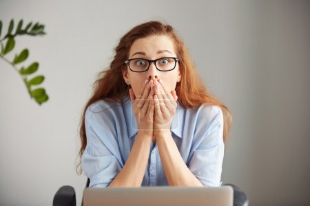 Photo for Portrait of young shocked businesswoman covering her mouth in surprise sitting in front of the laptop computer looking at the camera against grey wall background. Funny face expression human emotion - Royalty Free Image