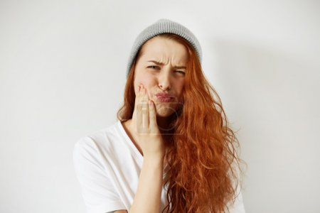 woman pressing cheek with painful expressio