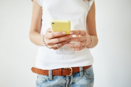 Selective focus. Close up view of woman's hands typing on mobile phone. Isolated shot of female wearing white sleeveless T-shirt and jeans reading news on cell phone while browsing Internet at home.
