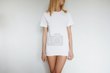 Photo for Close up portrait of slim Caucasian student girl wearing only white blank copy space T-shirt looking away while standing isolated against concrete blank studio wall. Cropped view. Lifestyle concept - Royalty Free Image
