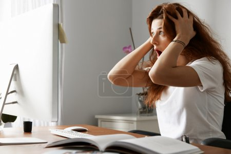 Stressed female freelancer screaming in shock, having serious computer problem. Horrified student girl clutching her head in panic, missing graduation project deadline, sitting in front of the laptop