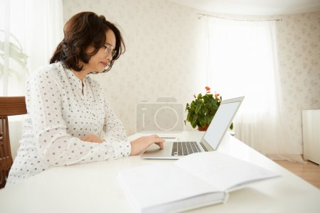 Side view of serious mature woman in glasses using wireless Internet connection on laptop, shopping online or reading news, sitting at the white table against home interior background. Selective focus