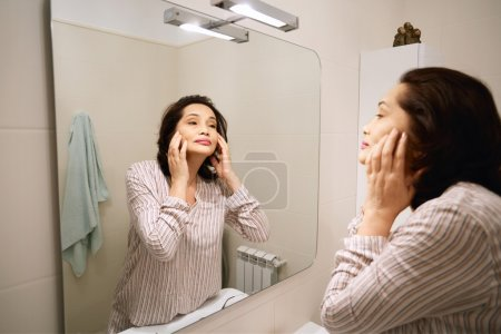 Mature brunette female applying make-up while doing morning routine procedures. Portrait of beautiful middle-aged woman wearing pajamas, looking at herself in the mirror. Beauty and health concept