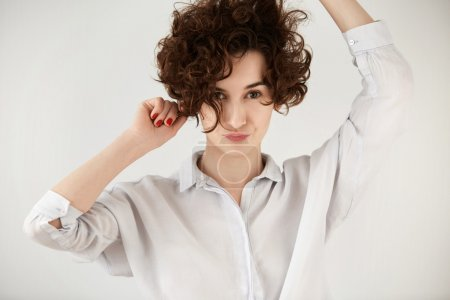 Portrait of attractive Caucasian hipster girl posing against white conrete wall with pounting lips. Student female with short curly hairstyle having fun while dancing to some pleasant music indoor