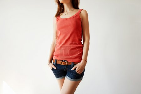 Close up portrait of young brunette female with beautiful fit body wearing red sleeveless top and denim shorts with hands in pockets standing isolated against white studio wall. Lifestyle concept