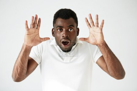 Portrait of stunned young African American man wearing white blank T-shirt looking at the camera in shock, surprised with some unexpected news, gesturing with hands. Human expressions and emotions