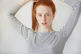 Beautiful Caucasian young woman with healthy freckled skin looking and smiling with thoughtful expression at the camera. Redhead girl wearing striped top posing iolated against white concrete wall