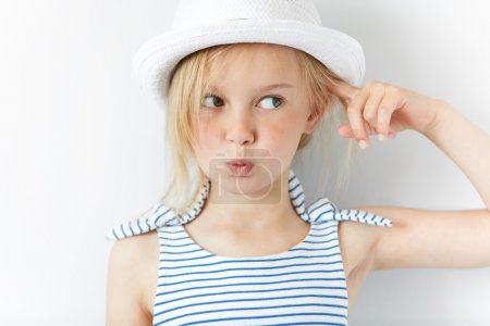 Headshot of angry and irritated preschool girl in white hat and striped dress, gesturing with index finger against her temple: are you crazy? Isolated portrait of little Caucasian 5-year old child
