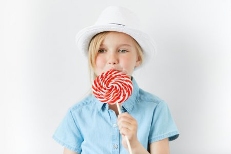 Isolated headshot of happy little female child with green eyes and blonde hair wearing white hat and denim shirt, posing with spiral lollipop in her hands, spending nice time with her parents indoor