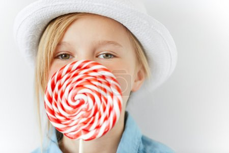 Close up portrait of adorable blonde little female child in white hat holding huge spiral sweet candy, having fun, enjoying  lollipop with happy expression, against white concrete wall. Selective focu