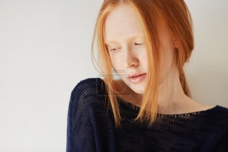 Beautiful female teenage model wearing casual black top looking down with shy and thoughtful expression on her face. Isolated portrait of coy redhead student girl with freckles and no make up