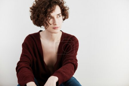 Portrait of Caucasian female with short curly hair cut, wearing casual cardigan with low neckline, looking away while posing against white concrete wall background for your text or promotional content