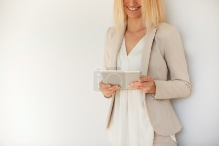 Pretty blond businesswoman in formal suit communicating with her partners via digital tablet computer standing against white studio wall background with copy spcae for your text or advertising content
