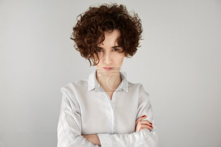 Angry businesswoman with brown curly hair looking at camera with sceptical and displeased expression, arms crossed. Portrait of beautiful female boss disappointed or angry with her office workers