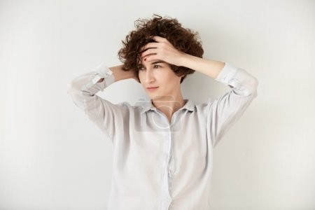 Close up shot of young beautiful female with thougtful expression looking away, dreaming about travelling. Pretty hipster girl with dark curly hair wearing white casual shirt posing with hands on head