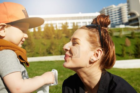 Portrait of happy redhead mother playing with her two-year old son wearing stylish cap during nice walk in the park on sunny day. Young female having fun with her baby boy. Family relations concept